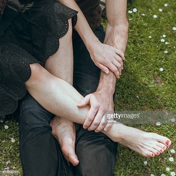 close up of mature man holding a mature woman's feet in his hand - man touching womans leg stock photos and pictures