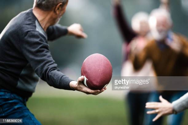 close up of mature man playing rugby with his friends in nature. - throwing stock pictures, royalty-free photos & images