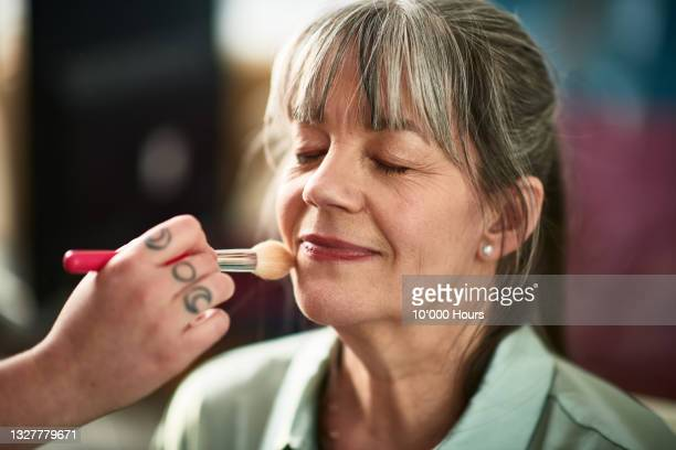 close up of mature woman's face with make-up brush - working seniors stock pictures, royalty-free photos & images