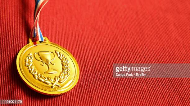 close up of medal on red fabric - 金メダル ストックフォトと画像