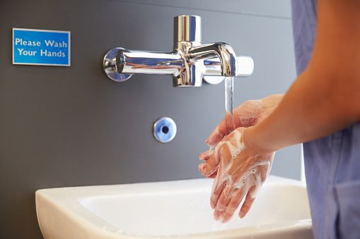 Close Up Of Medical Staff Washing Hands 489341254