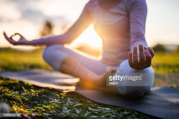 close up van meditatie in park bij zonsopgang. - yoga stockfoto's en -beelden