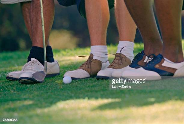 Close up of men's feet on golf course