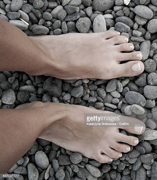 Close Up Of Mens Feet On Pebble Stones