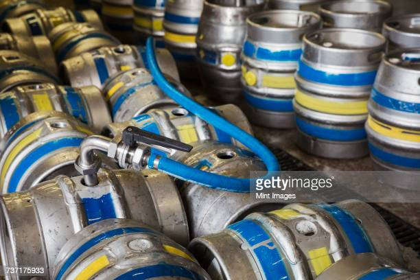 Close up of metal beer kegs being filled in a brewery.
