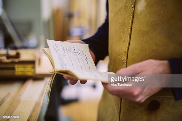 Close up of mid adult craftsman holding notebook in organ workshop