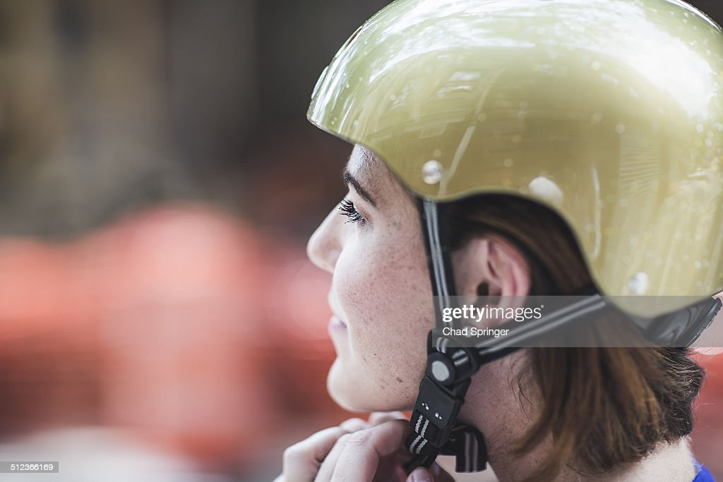 Close up of mid adult woman cyclist fastening cycle helmet : Stock Photo
