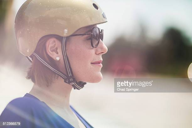 Close up of mid adult woman cyclist wearing cycle helmet and sunglasses