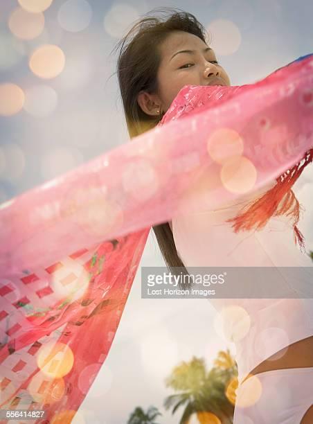 Close up of mid adult woman holding up pink scarf, Ari Atoll, Maldives