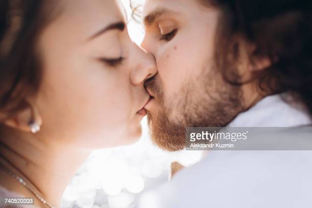 close up of middle eastern couple kissing - キス ストックフォトと画像