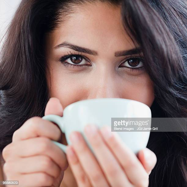 Close up of Middle Eastern woman drinking coffee