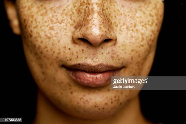 close up of middle of a mixed race woman's face with freckles - close to stock pictures, royalty-free photos & images