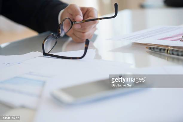 Close up of mixed race businessman holding eyeglasses at desk
