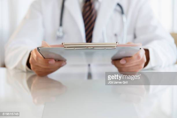Close up of mixed race doctor holding clipboard