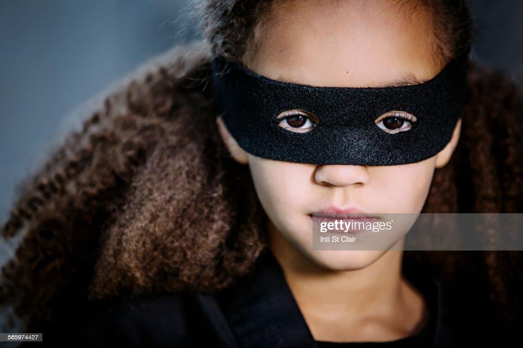 Close up of mixed race girl wearing mask : Stock Photo