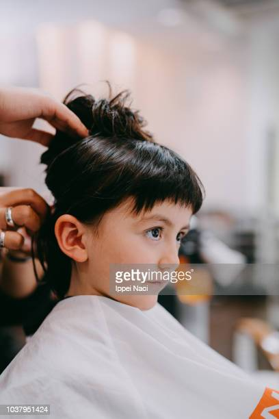 Close up of mixed race little girl at hairdresser