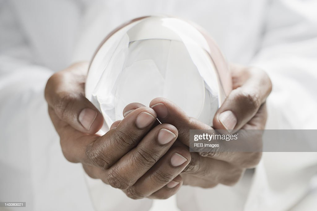 Close up of mixed race man holding crystal ball : Stock-Foto