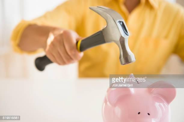 Close up of mixed race man holding hammer over piggy bank