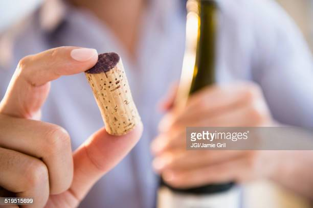 Close up of mixed race man holding wine cork