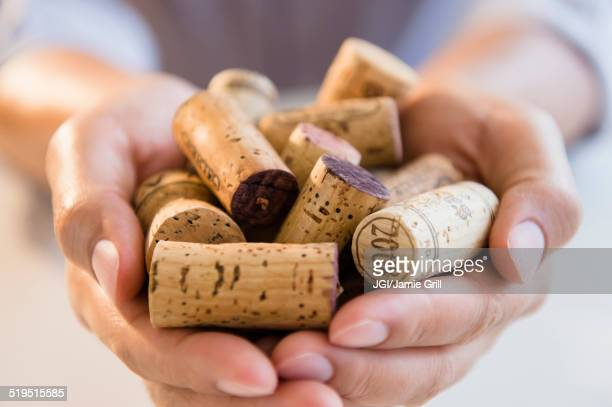 close up of mixed race man holding wine corks - wine cork stock photos and pictures