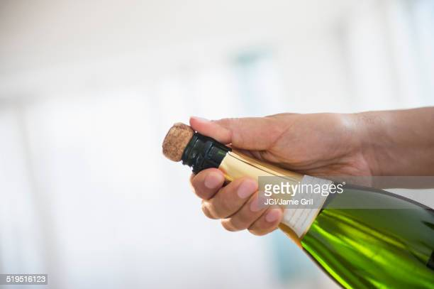 Close up of mixed race man opening bottle of champagne