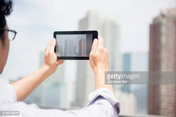 Close up of mixed race man photographing city skyline with digital tablet