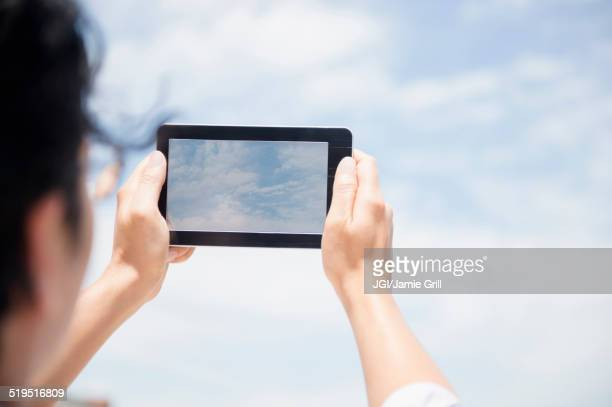 Close up of mixed race man photographing clouds with digital tablet