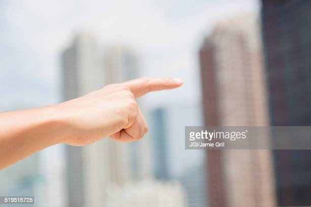 Close up of mixed race man pointing to city skyline
