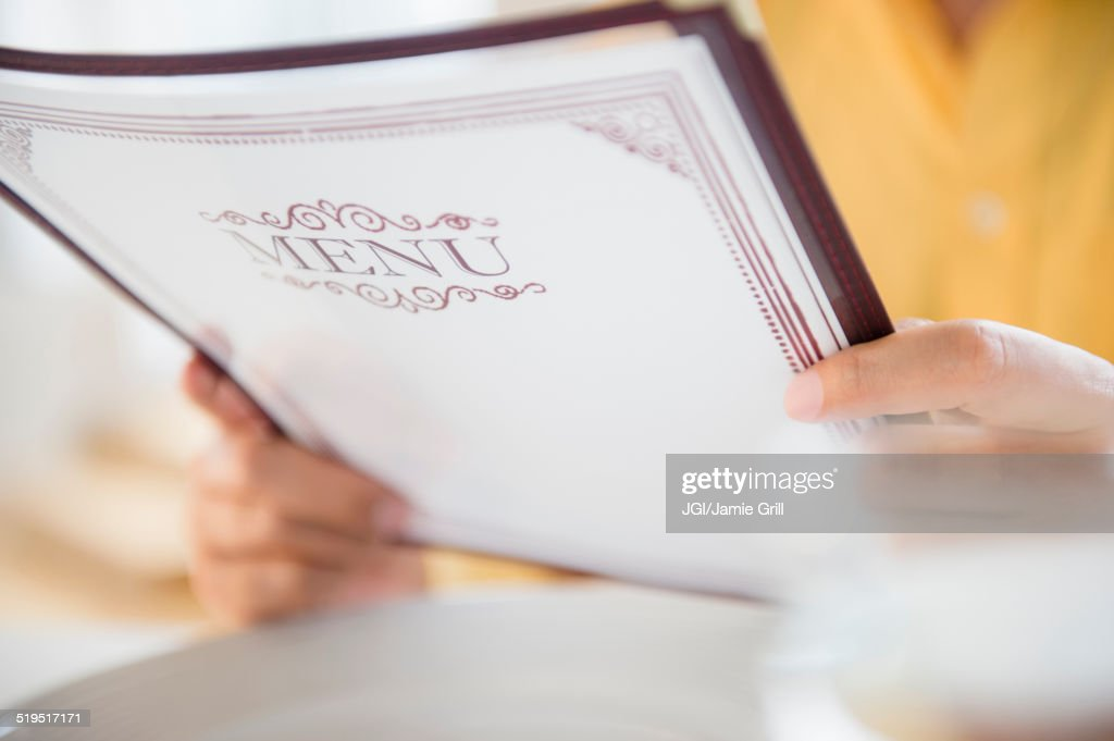 Close up of mixed race man reading menu in restaurant : Stock Photo