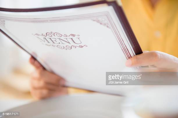 Close up of mixed race man reading menu in restaurant