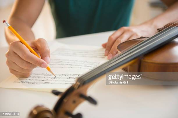 close up of mixed race man writing sheet music for violin - komponist stock-fotos und bilder