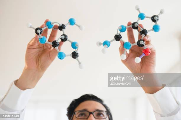 Close up of mixed race scientist holding molecular models