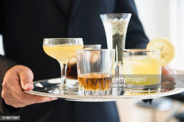 Close up of mixed race waiter holding tray of drinks