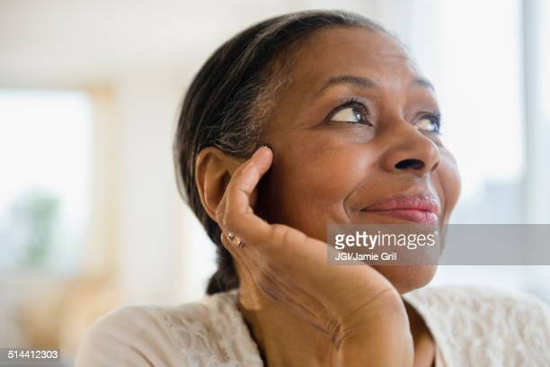 Close up of mixed race woman resting chin in hand