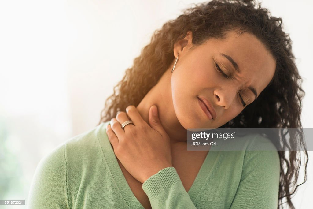 Close up of mixed race woman rubbing sore neck : Stock Photo