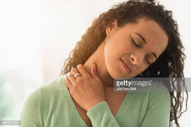 close up of mixed race woman rubbing sore neck - massage black woman stock photos and pictures