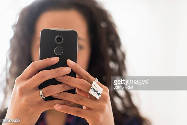 Close up of mixed race woman using cell phone