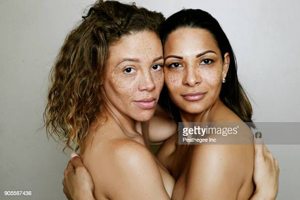 close up of mixed race women hugging - 30 39 jaar stockfoto's en -beelden