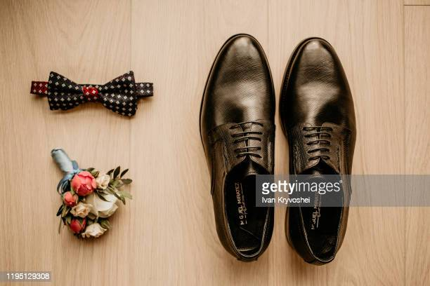 close up of modern groom accessories. black bowtie, leather shoes and flower boutonniere on rustic background. set for formal style of wearing isolated on white background - retrato formal stock pictures, royalty-free photos & images