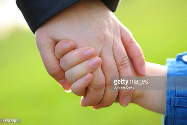 Close up of mother and daughter holding hands