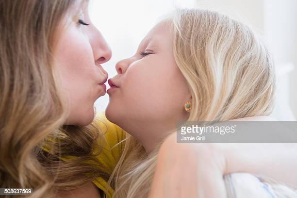 close up of mother and daughter kissing - kussen met de mond stockfoto's en -beelden