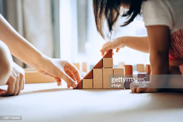 close up of mother and little daughter sitting on the floor playing with wooden building blocks together and enjoying family bonding time at home - 教育 ストックフォトと画像