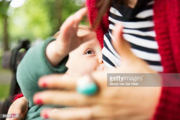close up of mother breastfeeding, baby playing with mothers hand while drinking. - breastfeeding stockfoto's en -beelden
