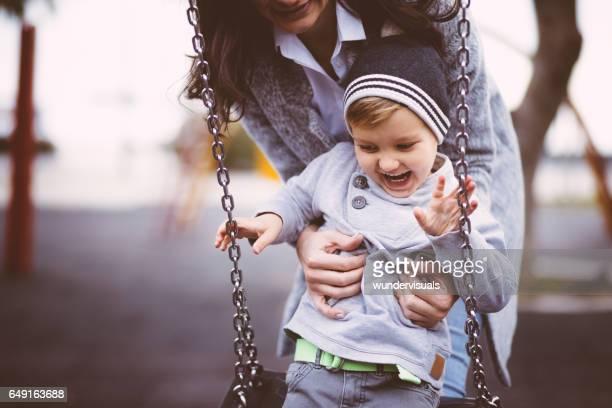 Nahaufnahme von Mutter umarmt Baby Boy auf einer Schaukel