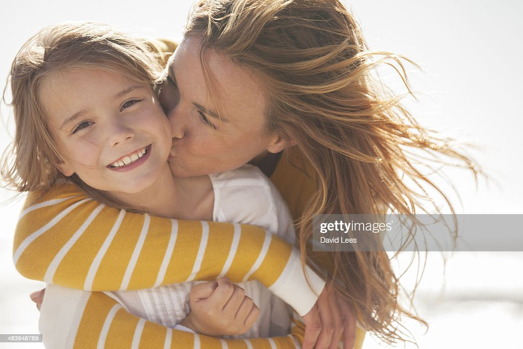 Close up of mother kissing daughter at beach : Foto de stock