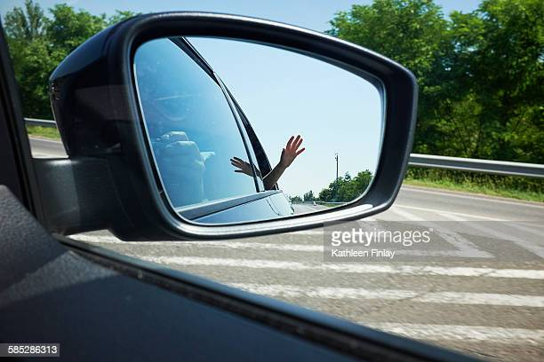 Close up of mother photographing sons hand reflected in wing mirror