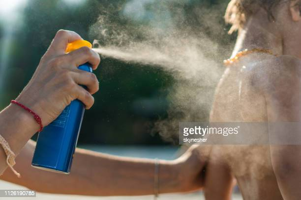 close up of mother protecting her son with suntan lotion at the beach. - spraying stock pictures, royalty-free photos & images