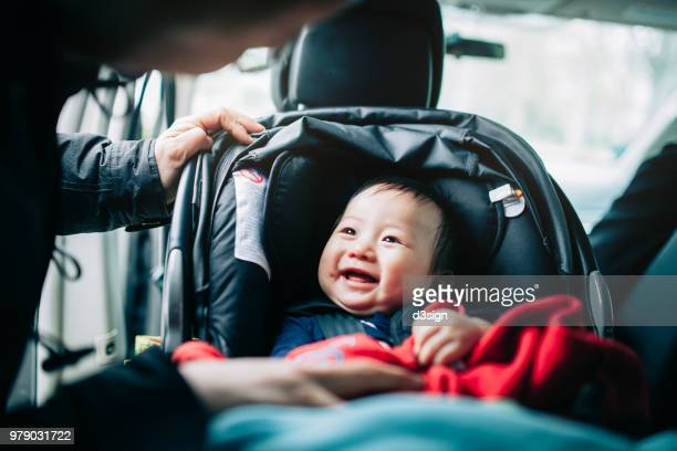 close up of mother taking care of cute smiling baby on car seat in car - asian baby stockfoto's en -beelden