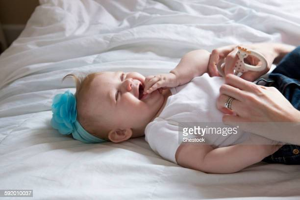 close up of mother tickling baby girl on bed - tickling stock pictures, royalty-free photos & images