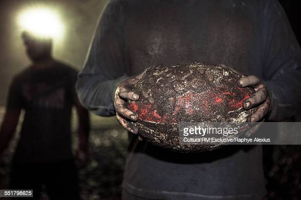 Close up of muddy ball in rugby players hands